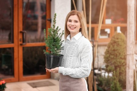 Business owner holding pot with plant near her store, outdoors