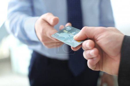 Businessman giving credit card to man, closeup