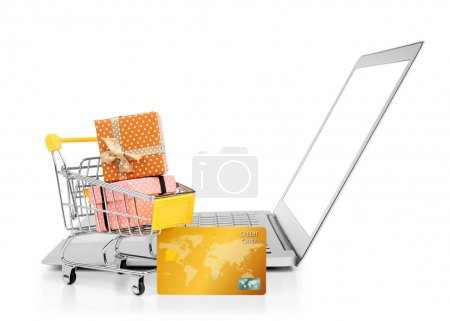 Laptop, credit card and small shopping trolley with gift boxes on white background. Internet shopping concept