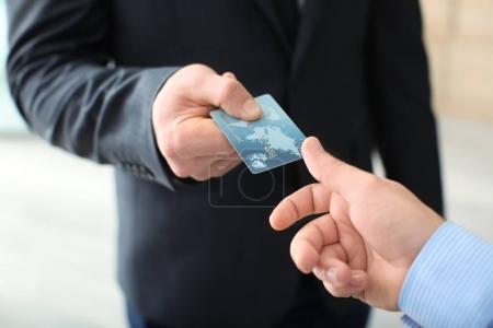 Businessman giving credit card to man, closeup
