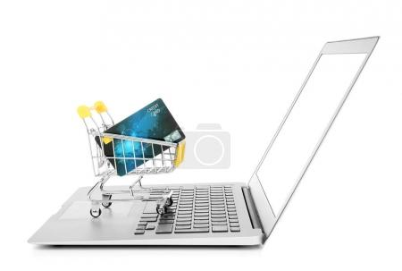 Laptop and small shopping trolley with credit card on white background. Internet shopping concept