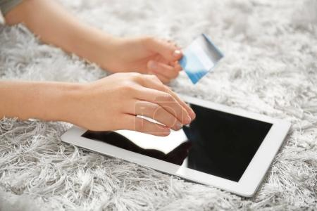 Woman holding credit card while using tablet computer at home, closeup. Internet shopping concept
