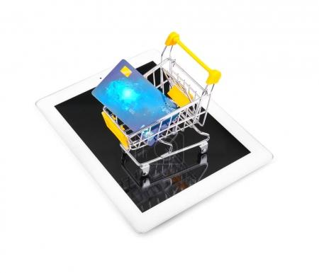 Tablet computer and small shopping trolley with credit card on white background. Internet shopping concept