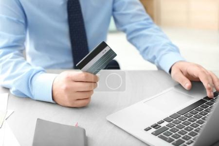 Man with credit card and laptop at table