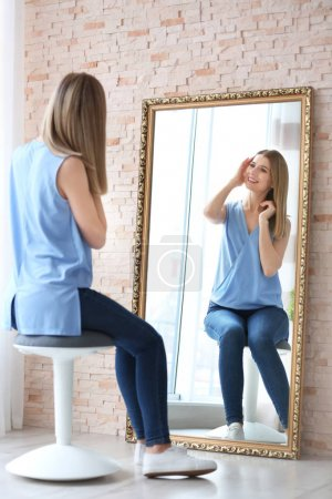 Young woman looking at herself in mirror indoors