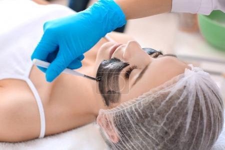 Cosmetologist applying carbon nanogel on woman's face, closeup. Peeling procedure