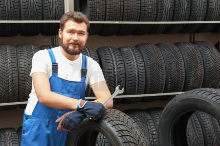 Male mechanic with spanner and car tire in automobile shop