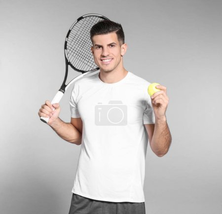 Portrait of handsome man with tennis racket and ball against grey background