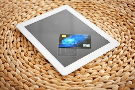 Tablet computer and credit card on wicker background. Internet shopping concept