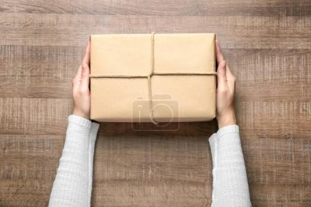 Photo for Woman with parcel box on wooden background - Royalty Free Image