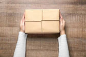 Woman with parcel box on wooden background