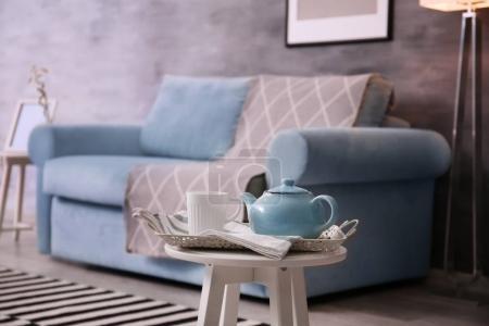 Stylish table with tea set near cozy sofa in living room interior