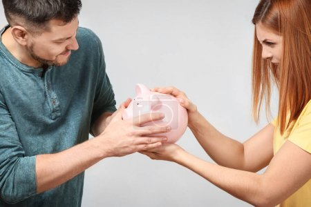 Couple arguing about planning of family budget against light background