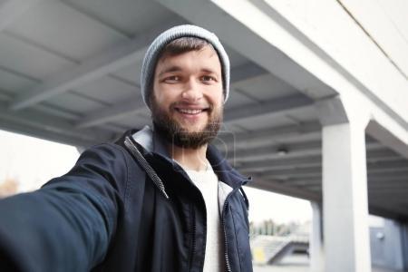 Photo pour Homme tendance hipster prenant selfie à l'extérieur - image libre de droit