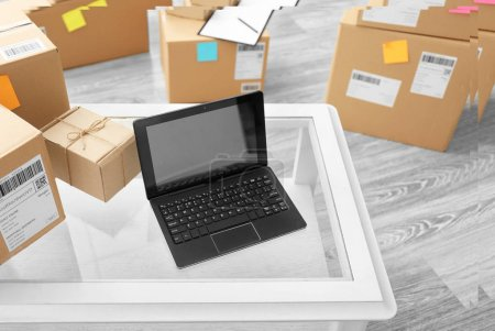 Laptop on table and parcels ready for shipment to customers in home office. Startup business
