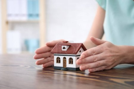 Real estate agent with house model at table. Insurance concept