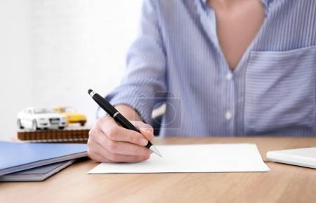 Woman filling in car insurance form at table