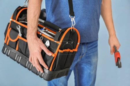 Young plumber with tool bag and pipe wrench on color background