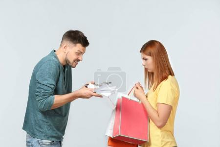 Angry man scolding his wife who has spent a lot of money for shopping, against light background