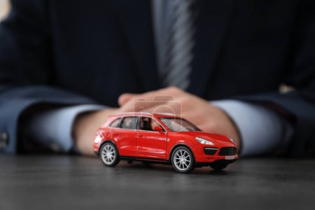 Man with car model at table. Insurance concept