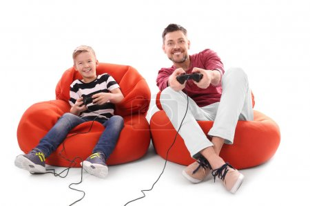 Photo for Cute boy with father playing video game on white background - Royalty Free Image