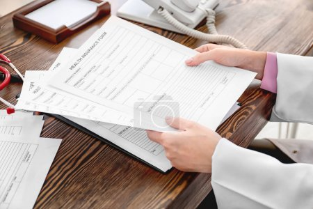 Female doctor working with documents in office. Health insurance concept