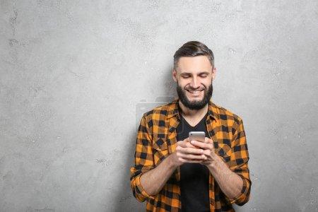 Photo pour Portrait d'un bel homme avec téléphone portable sur fond gris - image libre de droit