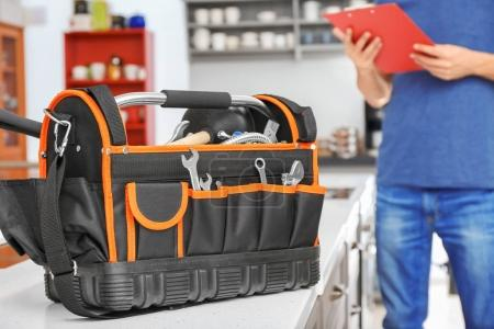 Young plumber with tool bag, indoors