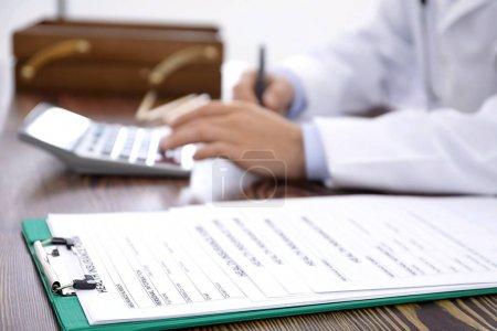Photo pour Presse-papiers avec formulaires d'assurance maladie et médecin à table - image libre de droit