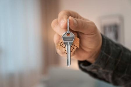 Man holding house key on blurred background, closeup