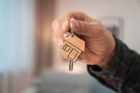Man holding house key on blurred background, closeup