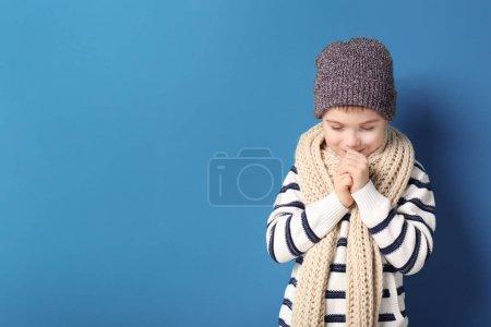 Photo pour Mignon petit garçon en vêtements chauds sur fond de couleur. Prêt pour les vacances d'hiver - image libre de droit