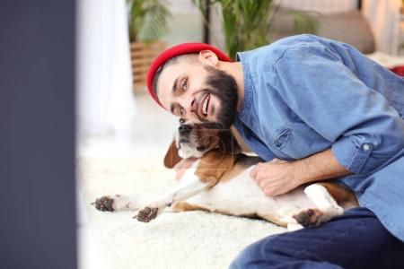 Handsome young hipster with dog at home