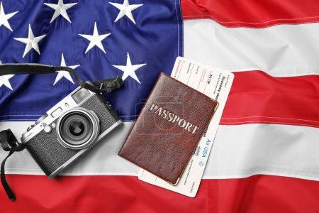 Passport with ticket and camera on USA flag. American visa concept