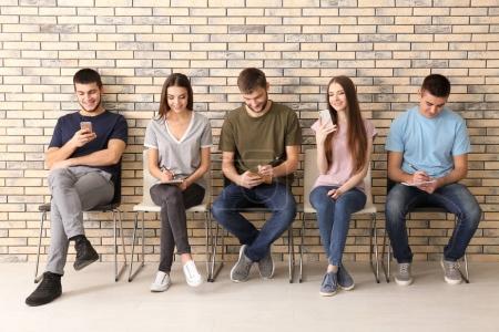 Photo pour Groupe de jeunes assis sur des chaises ensemble, à l'intérieur. Concept d'unité - image libre de droit