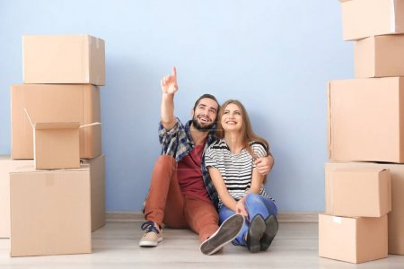 Photo for Young couple with moving boxes on floor in room - Royalty Free Image