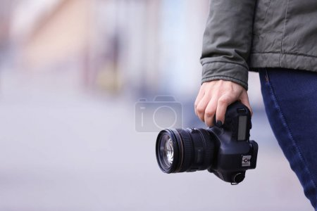 Young photographer with camera, outdoors