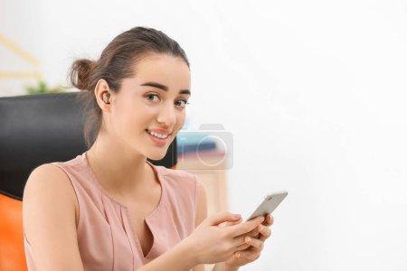 Photo pour Jeune femme avec utilisation de smartphone à l'intérieur de la prothèse auditive - image libre de droit