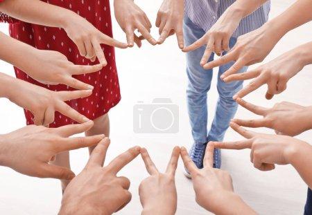 Photo pour Jeunes gens faisant cercle avec leurs mains comme symbole de l'unité - image libre de droit