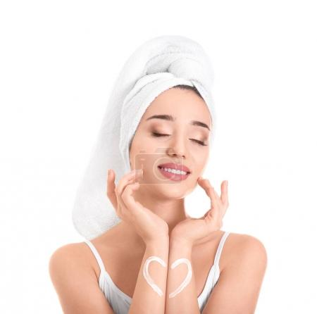 Young woman applying face cream on white background