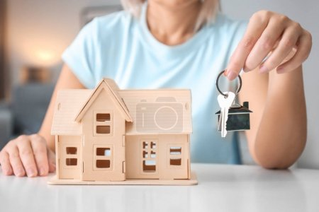 Woman holding key near house model, closeup