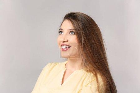 Portrait of beautiful happy woman on light background