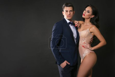 Sexy woman in underwear and businessman wearing suit on dark background