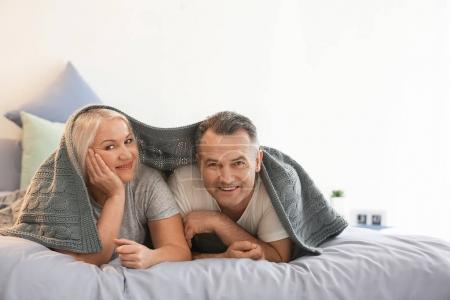 Photo pour Couple aîné sous plaid sur le lit ensemble - image libre de droit