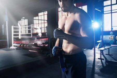 Boxer applying hand wraps while preparing for training in gym
