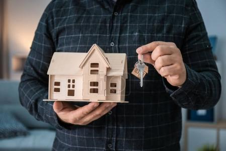 Man holding house model and key on blurred background, closeup