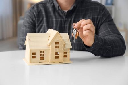 Man holding key near house model, closeup