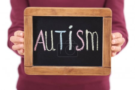 "Woman holding blackboard with word ""AUTISM"", closeup"