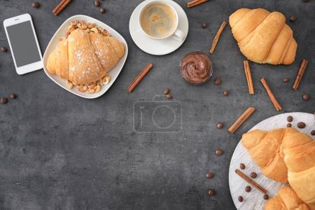 Photo for Tasty croissants, cup of coffee and smartphone on table - Royalty Free Image