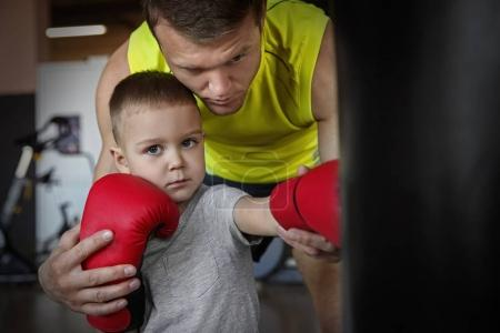 Little boy training with coach and punchbag in boxing gym